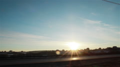 View from the left side car window driving at sunset Stock Footage