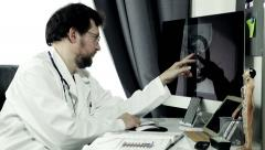 Worried doctor checking tumour on xray skull of patient - stock footage
