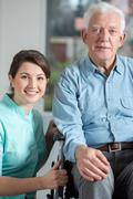 Disabled man and social welfare worker - stock photo