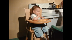 Boy in highchair eating 1950s with mother and older brother Stock Footage