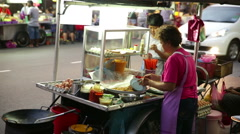 Street food vendor prepares noodle dish Chulia St, Penang Stock Footage