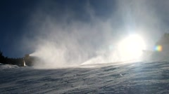 Snow making on slope. Skier near a snow cannon making fresh powder snow. - stock footage