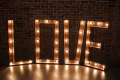 Three-dimensional letter LOVE with glowing lights - stock photo