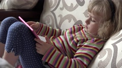 Smart Little Girl Using Tablet Computer while Sitting on Couch. 4k Ultra HD - stock footage