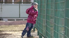 Little Girl Running Next to Metal Grid. 4k Ultra HD Stock Footage