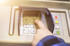 Close-up of hand entering PIN, pass code on ATM, bank machine keypad - stock photo