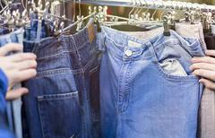 close up of  hands, looking for pants, jeans on a flea market - stock photo