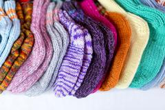 A  row of multicolored hand-knitted baby socks Stock Photos