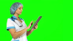 young female medical nurse using tablet computer on green screen - stock footage