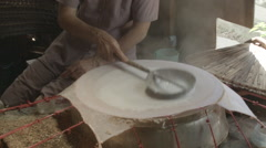 A woman pouring liquified rice paper on a steamer in Vietnam Stock Footage