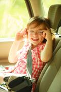 Transportation. Little girl child kid sitting in the car Stock Photos
