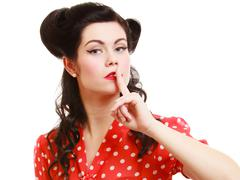 Retro. Pinup girl with finger on lips asking for silence Stock Photos