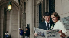 Bride and groom reading the newspaper Stock Footage