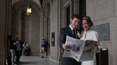 Happy Bride and Groom reading newspaper Stock Footage