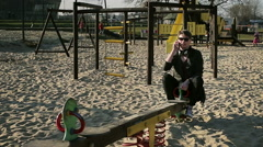 Student swing on seesaw and chatting on cellphone Stock Footage
