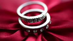 Two rings lie on a red bow Stock Footage