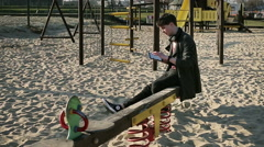 Student sitting on seesaw on playground and using tablet Stock Footage