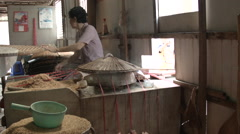 A woman making rice paper in the traditional way in Vietnam Stock Footage