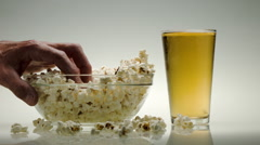 A HAND DESTROYS A BOWL OF POPCORN & A PINT OF BEER.  TIME LAPSE THIRST QUENCHER. Stock Footage