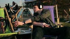 Student listening music and drinking beer in outdoor bar Stock Footage