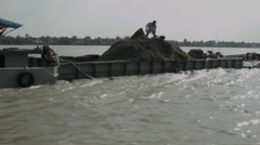 A man shovelling sand on a boat floating down the Mekong River in Vietnam Stock Footage