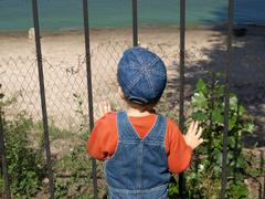Little boy looking from fence - stock photo