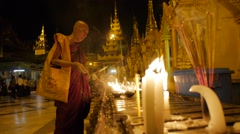 Monks lighting candles at Schwedagon Pagoda,Yangon,Burma Stock Footage