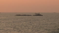 Archipelago of tiny low-lying islands tracking past at sunset - stock footage
