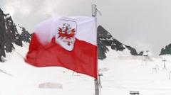 Austrian flag with thermal blankets on alpine glacier in background Stock Footage