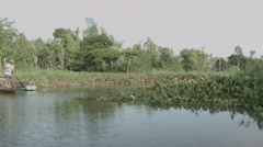 A man standing and rowing in boat down the banks of the Mekong river in Vietnam. Stock Footage