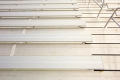 Empty bleacher seating in rows, taken in a modern school sports stadium facil Stock Photos