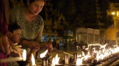 Girls lighting candles at Schwedagon Pagoda,Yangon,Burma Stock Footage