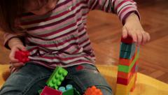 Little female child sitting on floor and playing with colorful dices, tilt up. Stock Footage