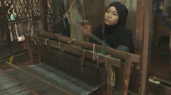 A Cham Muslim woman weaves on wooden loom on banks of Mekong river in Vietnam Stock Footage