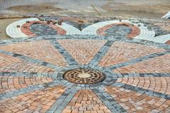 Manhole on paving tiles Stock Photos
