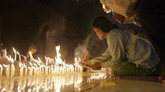 Lady lighting candles at Golden Rock,Kyaiktiyo,Burma Stock Footage