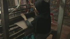 Stock Video Footage of A Cham Muslim woman weaves on wooden loom on banks of Mekong river in Vietnam