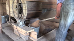 Peasant worker scoop sifted grain with shovel to metal bucket - stock footage