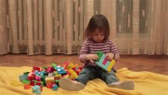 Hyperactive little girl sitting on floor and playing with colorful dices. Stock Footage