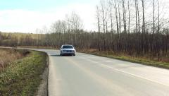 Car quickly passes on country road Stock Footage