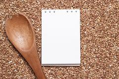 Buckwheat with brown wooden spoon and notepad Stock Photos