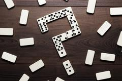 domino pieces forming question mark on wooden table - stock photo