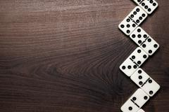 domino pieces forming zigzag over wooden table - stock photo
