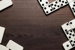 Domino pieces over wooden table background Stock Photos
