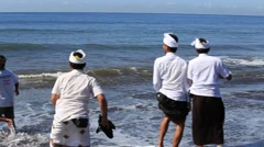Balinese men bring gift the gods the sea ducks, food and gifts the beach in Bali Stock Footage