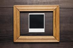 empty frame and old photo on wooden background - stock photo