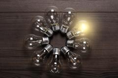 glowing bulb on wooden background uniqueness concept - stock photo