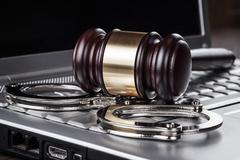 Handcuffs and judge gavel on computer concept Stock Photos