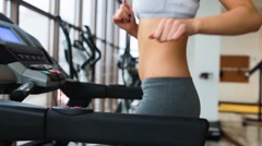 Girl with beautiful belly on the treadmill Stock Footage