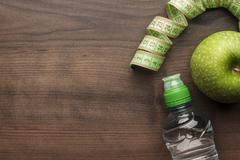 bottle of water measuring tape and fresh green apple - stock photo